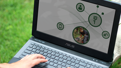Notebook im Gras mit Bildschirmoberfläche zur Digitalisierung